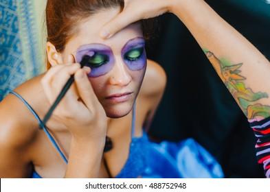 Makeup artists in work making a Halloween makeup - mexican Santa Muerte mask.