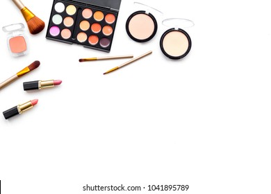 Makeup background. Eyeshadow palette, rouge, powder, brushes, lipstick on white background