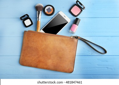 Makeup bag with beauty products and phone on wooden background