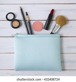 Make-up bag with products spilling out on a wooden background