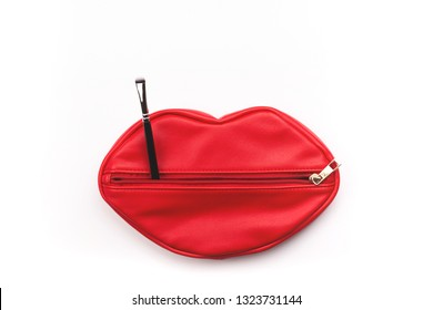 Makeup bag in red lips shape and brush on white background. Creative beauty and cosmetics concept.