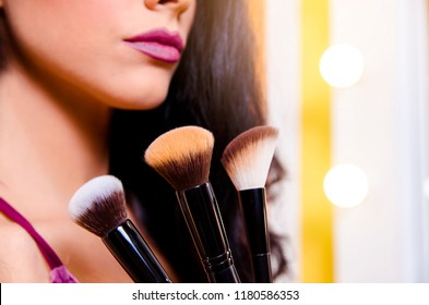Makeup up / beautification concept , closeup of unrecognizable woman face with makeup on and brushes in foreground