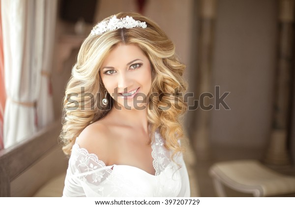 Makeup. Beautiful smiling Bride wedding Portrait with wedding hairstyle, Wedding dress. Wedding decoration. soft selective focus. gorgeous young woman at home