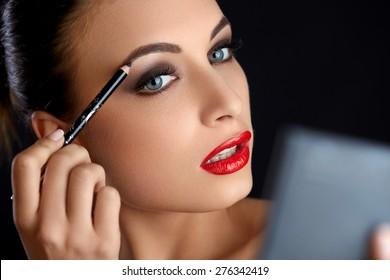Make-up. Beautiful Woman Doing Makeup Eyebrow Pencil. Red Lips