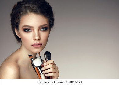 Makeup Beauty Cosmetics. Closeup Of Beautiful Young Woman With Glamorous Eyes Makeup, Fashionable Hairstyle Holding Make-Up Brushes. Portrait Of Sexy Female Model With Cosmetic Tools. High Resolution