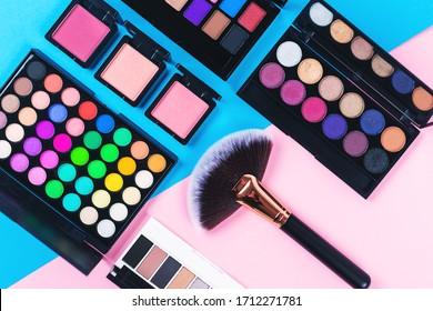ピンクと青の背景に化粧品と美容品。アイシャドウパレット。扇風機がブラシとブラッシュをこぼしている。平面図、上面図。