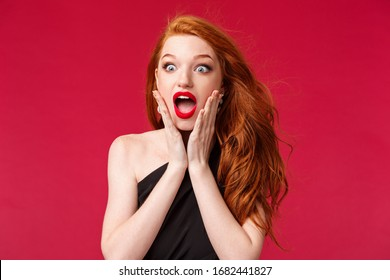 Makeup, beauty and women concept. Close-up portrait of astonished speechless redhead beautiful girl seeing something beautiful and awesome want to have it, losing speech, touch cheeks and drop jaw