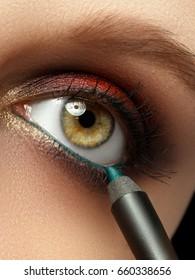 Make-up with black eyeliner close-up. Make-up artist applying eyeliner pencil on a model with green eyes