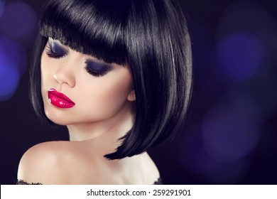 Makeup. Bob short hairstyle. Sexy girl model with naked shoulder posing over dark background. Blue eyeshadows closup.