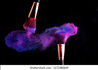 Make-up brush with colorful powder splashes explosion on black background