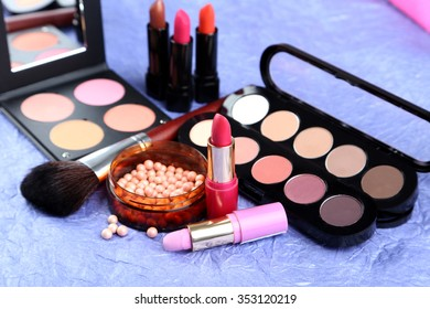 Makeup brush and cosmetics on a blue background