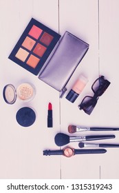 Makeup brush and cosmetics, on a white background.