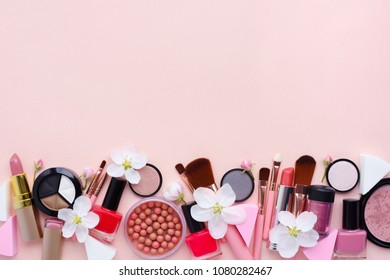 Makeup brush and decorative cosmetics with apple blossom on a pastel pink background with empty space. Top view
