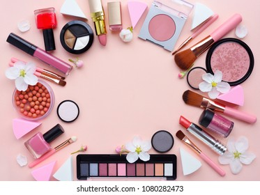 Makeup brush and decorative cosmetics with apple blossom arranged around a blank space on a pastel pink background. Top view