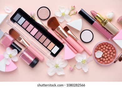 Makeup brush and decorative cosmetics with apple blossom on pink background. Top view
