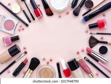 Makeup brush and decorative cosmetics arranged around a blank space on a pastel pink background. Top view