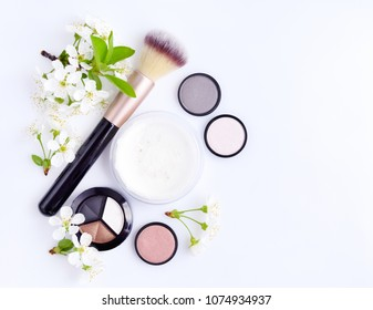 Makeup brush and decorative cosmetics with blooming branch on white background. Top view