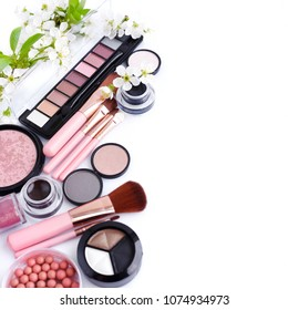Makeup brush and decorative cosmetics with blooming branch on white background with copy space