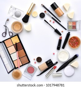 Makeup brush and decorative cosmetics on a white background with empty space in the middle. Top view
