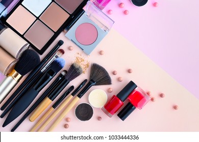 Makeup brush and decorative cosmetics on pink background with empty space. Top view