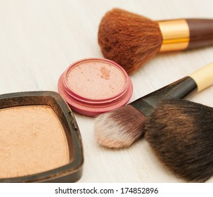 makeup brush and face powder on the table