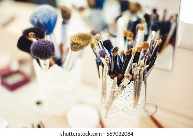 Makeup brush in a glass beaker on the dressing table.
