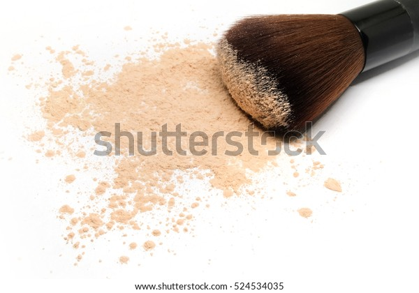 Makeup brush with loose cosmetic powder on white background.