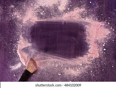 A makeup brush on a purple background, with traces of powder and blush on it forming a frame. A horizontal template for a makeup school business card or flyer design, with plenty of copyspace