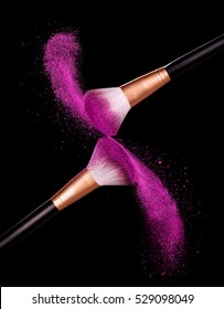 Make-up brush with pink powder dust on black background