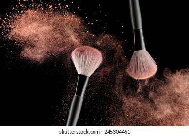 Make-up brush with pink powder explosion on black background - Shutterstock ID 245304451
