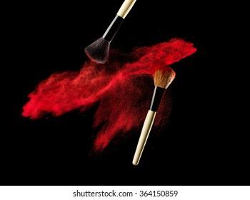 Make-up brush with powder explosion on black background