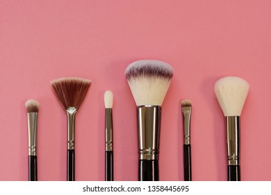 Makeup brush set, professional makeup tools, brushes for different functions. Fashion cosmetic accessories, pink background