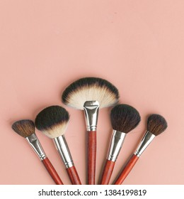 Makeup brush set, professional makeup tools, brushes for different functions on pink background
