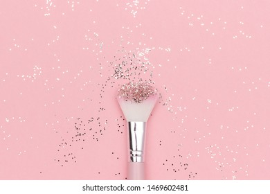 Makeup brush and shiny sparkles on pastel pink background. Festive magic makeup concept. Template for design, Top view Flat Lay Copy space.
