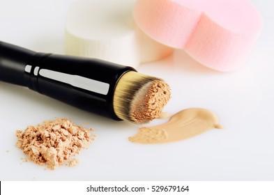 make-up brush, sponges, smear makeup base and face powder on a white background, horizontal orientation