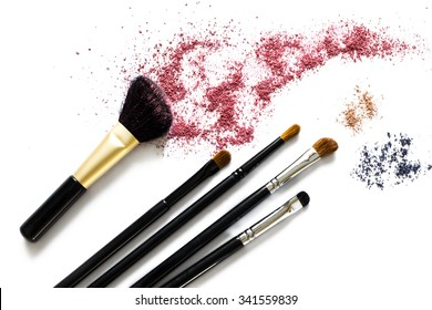 Makeup brushes with blusher and eyeshadow sample on white background