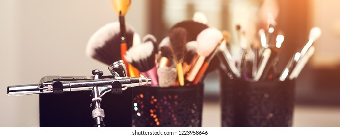 Makeup brushes, close up. Makeup airbrush and other tools on table. Make-up products set. Cosmetics and brushes on on artist workplace