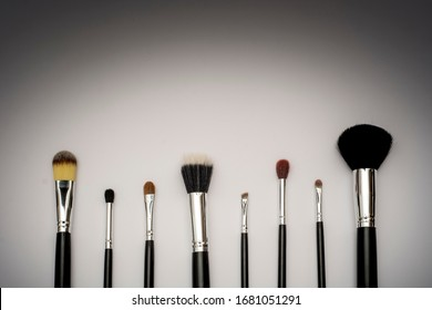 Makeup brushes of different sizes with gradient background