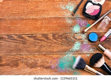 Make-up brushes, eye shadows, perfume bottle, lipstick and nail polish on a wooden background. Text space. Top view.