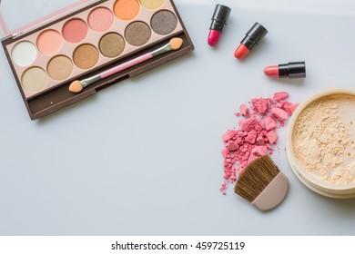 Make-up brushes, eye shadows,loose powder on white background.Pink and Orange lipstick.