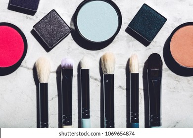 Makeup brushes and eyeshadows on a marble background. Beauty tools. Flat lay.