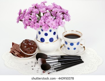 Makeup brushes, flowers in polka dot jug and cup of coffee with cupcake on white background