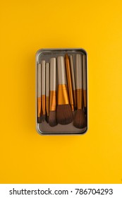 make-up brushes in an iron box on a yellow background