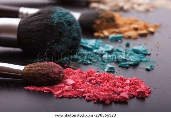 Makeup brushes on background with colorful powder. Crushed eyeshadow on black background. Abstract background. Selective focus.