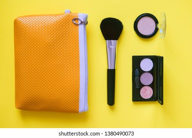 Make-up brushes on a bright yellow background.