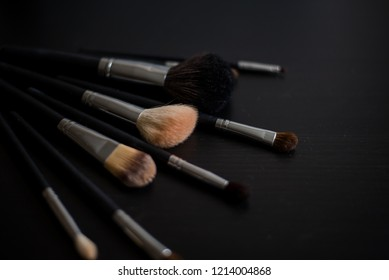 Makeup brushes on dark background spread out by fan, professional makeup brushes, makeup brushes set on black background (horizontally; warm toned)