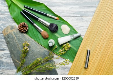 makeup brushes on leaf with lotion bottle on wood background, paintbrush beauty accessory, beauty product, cosmetics bottle containers