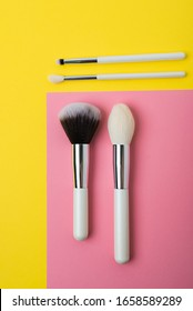 makeup brushes on a multi-colored background, pink and yellow