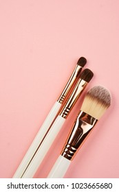 make-up brushes on a pink background