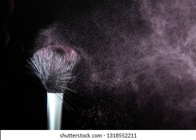 makeup brushes and powder in a balck background